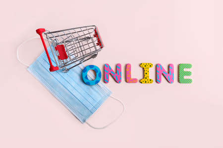 Word online from the multicolored letters and and blue medical mask.Shopping cart on background.Stay home concept.Backdrop for text or design.Contactless purchases. 版權商用圖片 - 148098562
