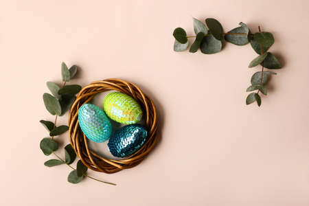 Colorful glossy easter eggs in the rattan nest.Natural eucalyptus branch on the back.Copy space for text or design.