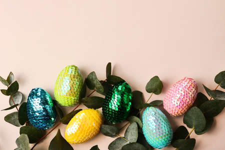 Colorful glossy easter eggs witih leafs of the natural eucalyptus.Trendy pastel background.Copy space for text or design.