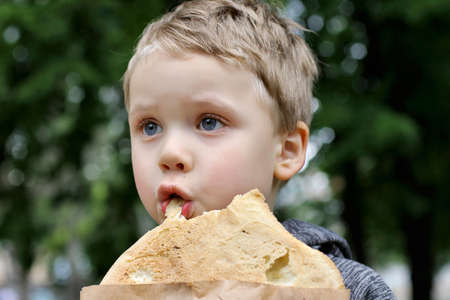 Funny blondheared toddler eating Georgian bread with appetite on the street.loseup photography of finny boy.Copy space for text. 版權商用圖片