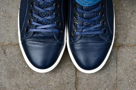 Top view of male blue sneakers on the asphalt road.Copy space for text.