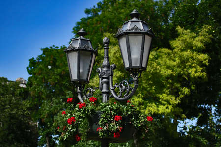 Antique lamppost in the park.Bright blooming flowers on the background.Beautiful city places.Copy space for text.Summertime.