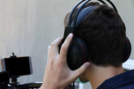 Closeup photography of a videographer working outdoor,holding his headphones and microphone.Face mask as protection from covid on the face.