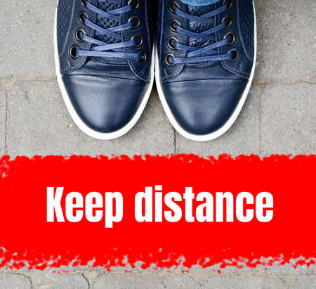 Top view on male navy blue sneakers standing on the pavement in front of the red line.Keep distance concept.Social isolation and distance during qaurantine 2020.