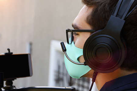 Closeup photography of a videographer working outdoor,with headphones and microphone.Face mask as protection from covid on the face. 版權商用圖片