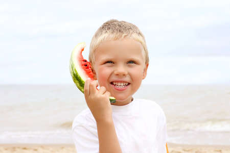 Cute blondheared toddler smiling and holding a slice of watermelon like a phone. 版權商用圖片 - 151871549