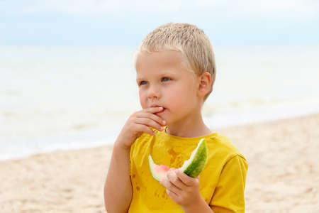 Sweet blonde kid on the coast, deep in his thoughts. Holds a slice of watermelon and looks ahead.Summertime concept. 版權商用圖片