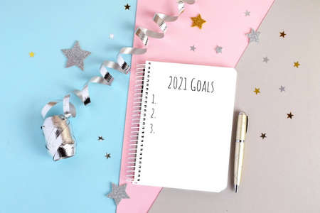 Triple pastel colors background with notebook and gold pen. Notebook with 2021 goals.Concept of making new year plans and resolutions.