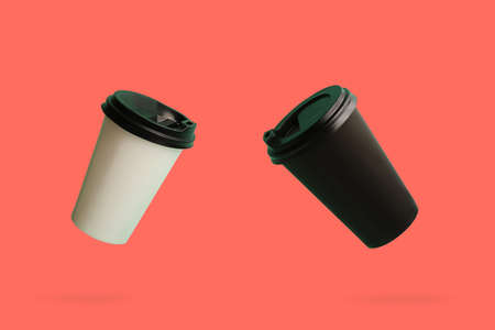 Two soaring paper cups of coffee on the coral background.
