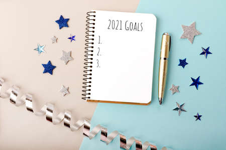 Isolated notebook and gold pen on the fstive vew year background.Notepad with 2021 goals.Conecept of making new year plans and resolutions. 版權商用圖片