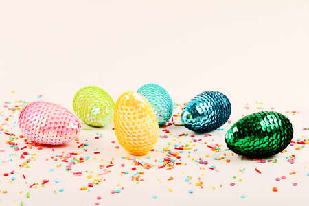 Colorful glossy easter eggs with sequins.Vivid pastry topping on the pastel background.Festive background.Free space for text.