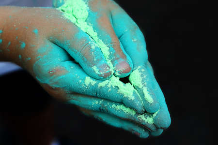 Child hands with dry holi paint.Colour powder for traditional indian festival.Close up photography,copy space.