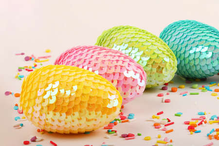 Multicolored cColorful glossy easter eggs with sequins.Vivid pastry topping on the pastel background.Festive background.Free space for text.Close up photography. Archivio Fotografico