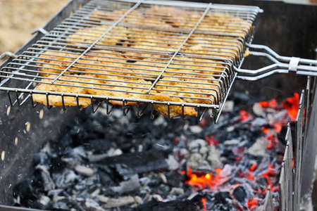 Pieces of meat laying on the mesh for a barbecue. Burning coals in the grill.Picnic in the city concept.Close up photography, copy space.
