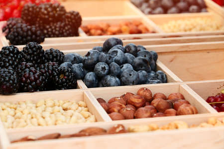 Assorted berries and nuts on a wooden platter. Blueberries, blackberries, almonds, hazelnuts and other nuts and berries.Close up photography.Outdoor picnic concept.