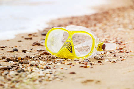 Close up photography of yellow snorkling mask standing in the sand.Underwater diving concept. 版權商用圖片