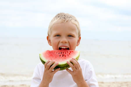 Sweet blonde kid on the coast, holding juicy slice of the watermelon. He looks ahead and wants to eat it.Summertime concept.