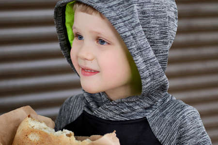 Funny blondheared toddler holding in the arms Georgian bread on the street.Happy smile on his face.Closeup photography of cute boy.Copy space for text.