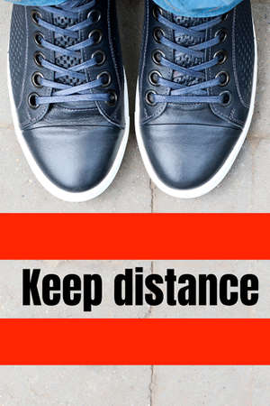 Top view on male blue sneakers standing on the pavement in front of the red line.Keep distance concept.Social isolation and distance during qaurantine 2020. 版權商用圖片