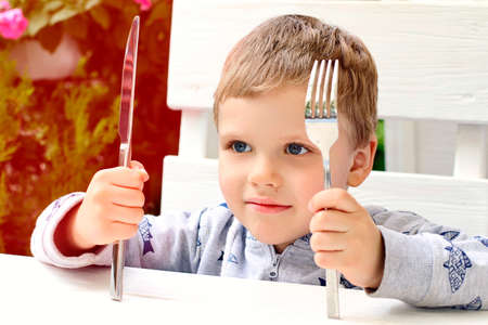 The child shows that he wants to eat. Kid holding fork and knife over the table. The interior in a modern restaurant outdoor. 版權商用圖片