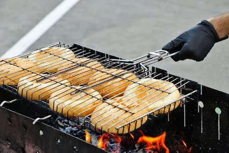 Hot mouthwatering toasted hamburger buns in the grill mesh.Young man preparing them on the brazier. 版權商用圖片