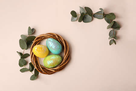 Colorful glossy easter eggs in the rattan nest.Natural eucalyptus branch on the back.Happy easter concept. Standard-Bild
