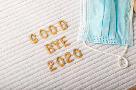 Close up golden letters good bye 2020 on the letter box.Blue medicine mask on it.Forgiveness with the current year concept.Creative layout. Banque d'images