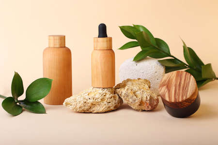 Composition from the natural materials and wooden cosmetics containers near it.Fresh green leafs on the background.Concept of the natural organic components.Advertising banner.Pastel colors.