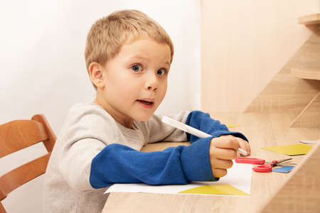 Funny boy with surprised face sit at the table,while drawing or writing.Home education concept or development activities.Online learning.