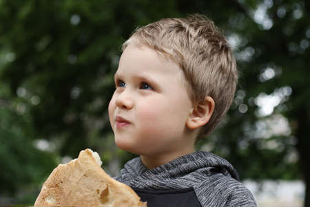 Funny blondheared toddler eating pita bread with appetite on the street.Closeup photography of cute boy with .Copy space for text. 版權商用圖片