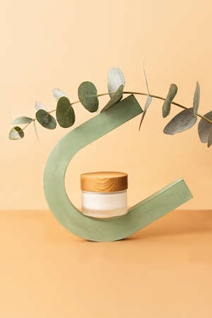 Glass skin care packaging with wooden cover balancing on the geometrical arch. Fresh eucalyptus branch on it. Pastel colors, cosmetics mockup concept.