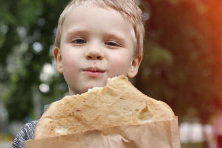 Funny blondheared toddler eating pita bread with appetite on the street and looks at the camera.Closeup photography of cute boy with .Copy space for text. 版權商用圖片