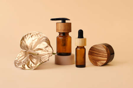 Various cosmetics containers with wooden caps, neutral beige background.Bottle from glass stays on the geometric podium, golden flamingo flower near it.Zero waste, organic concept.Modern minimalism.