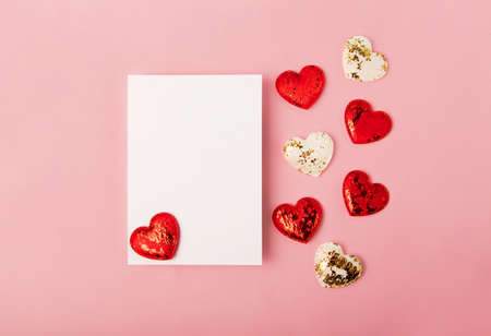 Isolated blank greeting card on the pink backround.Red and white hearts near it. Mockup with copy space.Good for 14 february.