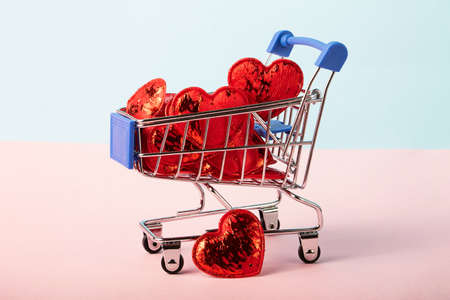 Shopping cart on the isometric pink and blue background full of glossy red hearts.Concept of the Saint Valentines day.