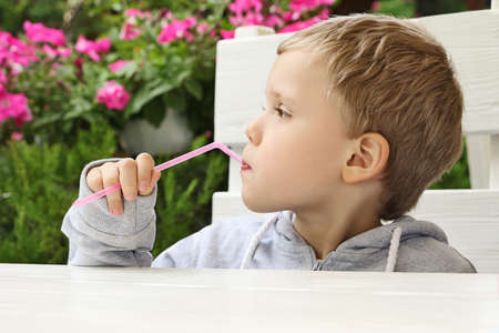 Pretty child holds straw and looking away.He sits at the table, on the restaurant terrace.Blooming flowers and fresh greenery behind. 版權商用圖片