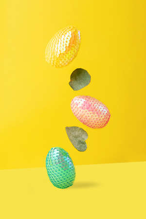 Flying multicolored Easter eggs on the trendy isometric yellow background.Vertical photography, creative card.