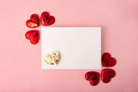 Isolated blank greeting card on the pink backround.Red and white hearts near it. Mockup with copy space.Good for 14 february, greeting for Valentines day. 版權商用圖片