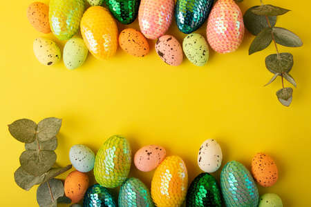 Frame made from multicolored easter eggs.Fresh eucalyptus branch near it.Trendy yellow background.Creative layout with copy space.