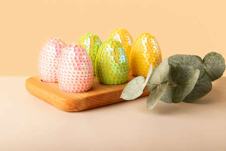 Multicolored glossy handmade eggs from sequins in the wooden tray.Eucalyptus branch behind.Trendy neutral beige isometric background.Easter cocnept.