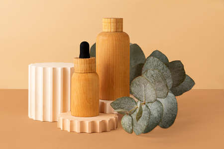 Wooden cosmetics containers on the pastel isometric background.Empty geometric shape podium and fresh eucalyptus branch behind.Earth colors, zero waste containers.Mockup concept, horizontal photography. 版權商用圖片