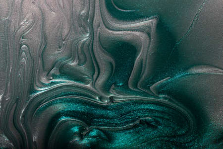 Silver and turquoise shimmer abstract background.Makeup concept.Beautiful stains of liquid nail laquers.Fluid art, pour painting technique.Good as digital decor, copy space.Horizontal photography.