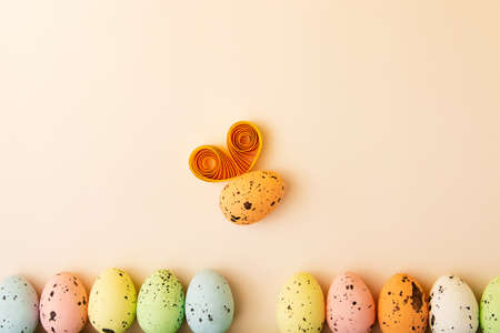 Row from multicolored eggs on the pastel background.Funny egg like a bumblebee with paper wings.Easter concept,creative layout.Funny greeting card with copy space. 版權商用圖片
