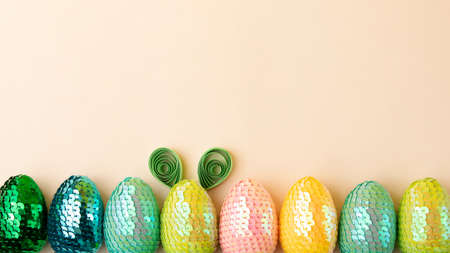 Row from multicolored eggs on the pastel background.One egg with rabbit ears made from paper.Minimal easter concept.Flat lay, copy space.