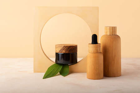 Cosmetics containers from wood and brown glass in the geometrical shape arch with green leafs. Concept of the zero waste packaging.Eco friendly cosmetic.Mockup concept, isometric background.