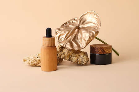 Composition from the natural stones, golden flamingo flower and cosmetics containers from wood and glass.Concept of the organic, zero waste materials.Beautiful beige palette.