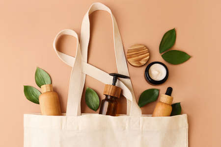 Open eco friendly cotton reusable bag with the different containers from the wood and glass.Pastel colors.Fresh natural leafs around.Concept of organic, zero waste cosmetics.Woman bag with accessories.