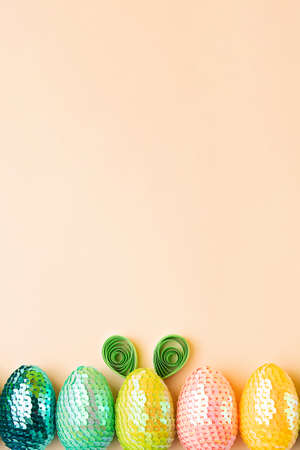 Row from multicolored eggs on the pastel background.One egg with rabbit ears made from paper.Minimal easter concept.Flat lay, copy space.Vertical photography. 版權商用圖片