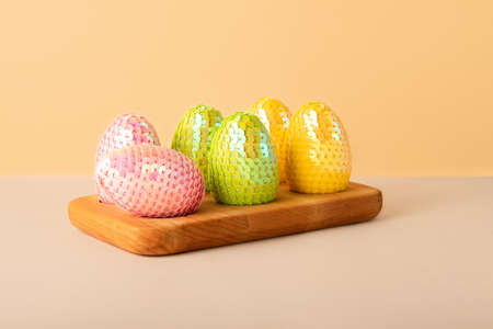 Multicolored glossy handmade eggs from sequins in the wooden tray.Trendy neutral beige isometric background.Easter cocnept.