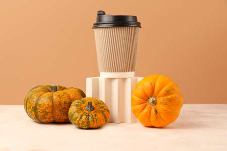 Assortment from pumpkins near geometrical podium with craft coffee cup.Concept of the spicy pumpkin coffee.Pastel colors, copy space. 版權商用圖片